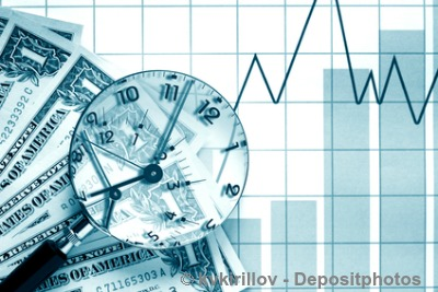 Clock inside magnifying glass near money on paper background with chart