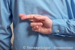 Man in blue shirt crossing his fingers at his back