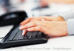 Woman's hand typing on black keyboard