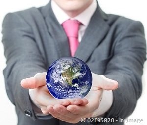 Man in a grey suit holding world globe in both hands