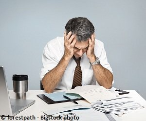 A business person who is very depressed after making a mistake
