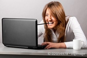girl typing on computer with a pencil in her teeth