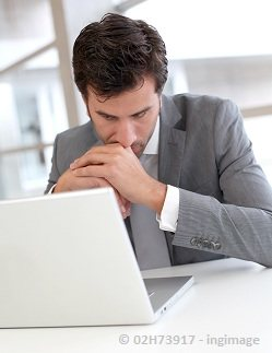 a businessman in deep thoughts while seriously looking on his computer screen